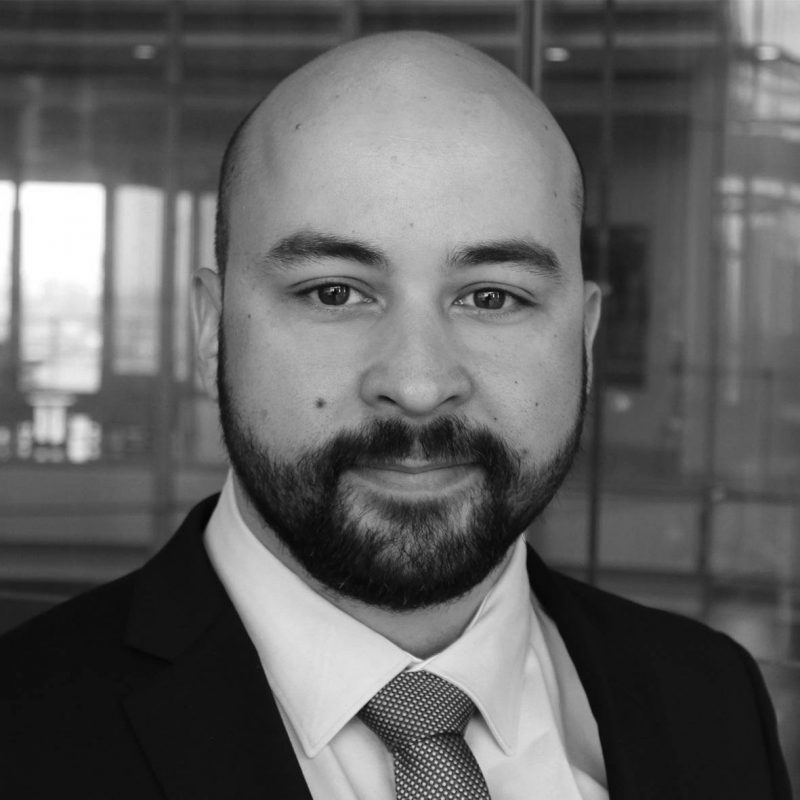 A black and white headshot of Seth Enoka, a Senior Industrial Incident Responder at the industrial cyber security company Dragos, Inc