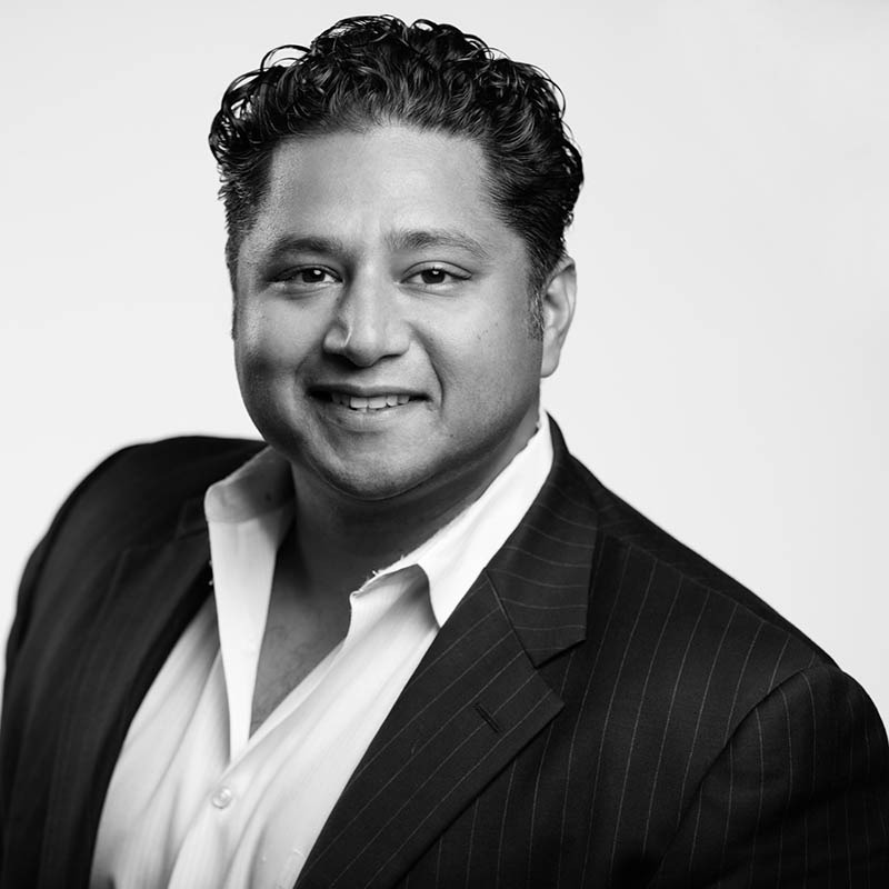 A black and white headshot of Sunny Sinha