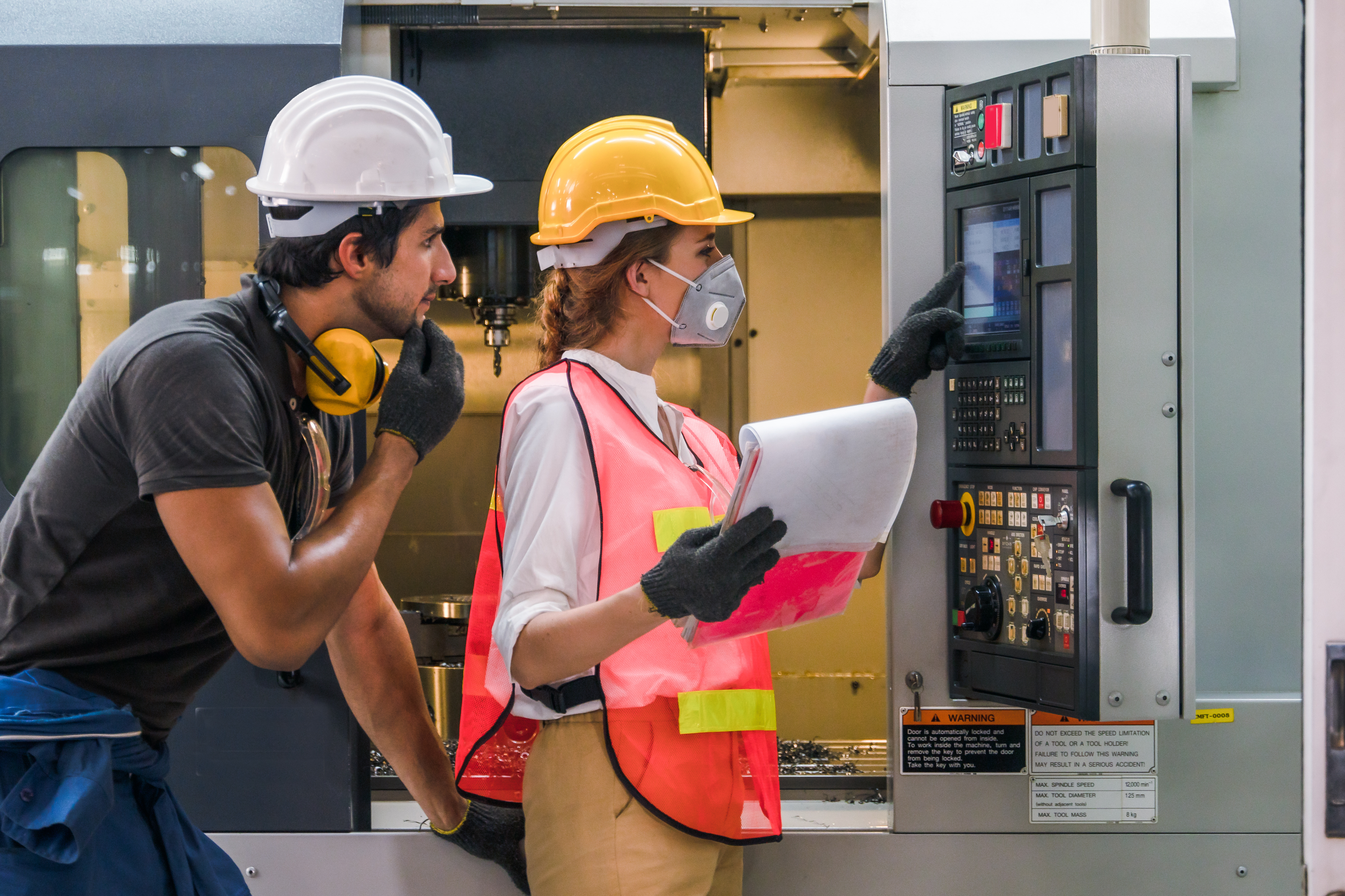 Two people in safety gear in front of an Engineer control panel