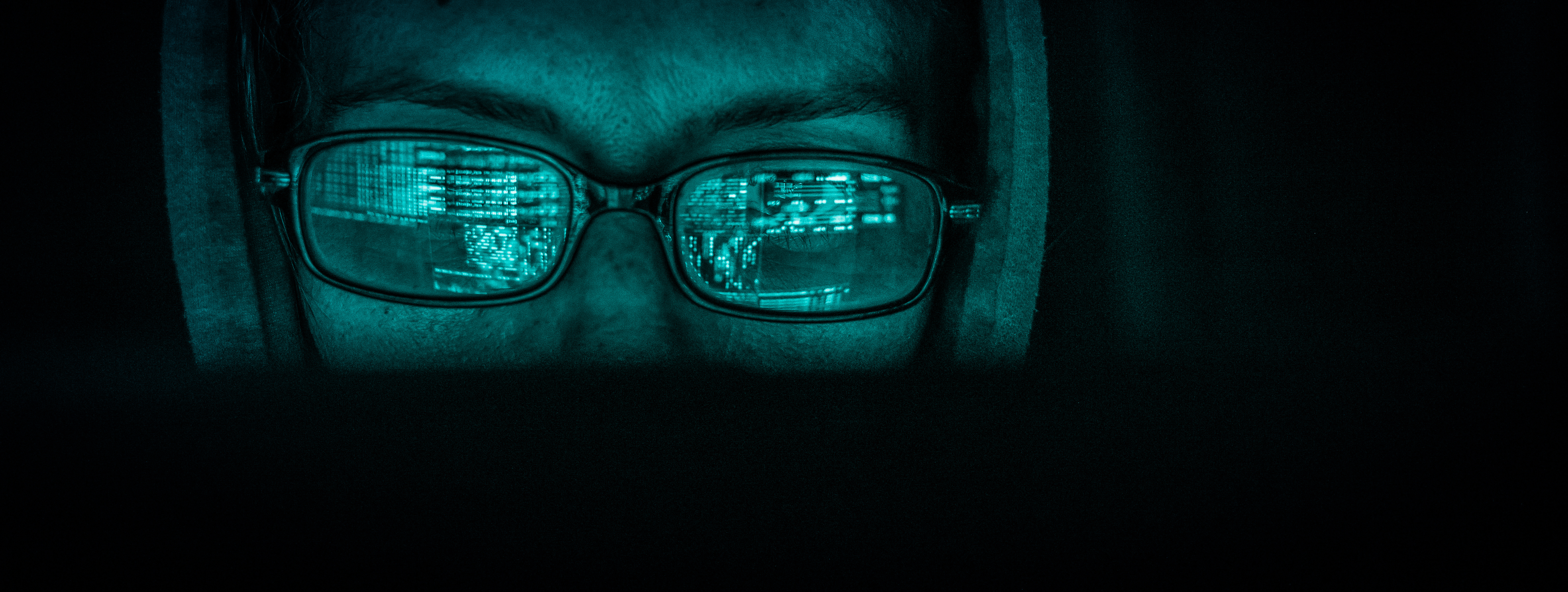 a photo of a person wearing rectangular glasses with a hoodie. The person has a glowing green filter over them to indicate they are adversarial