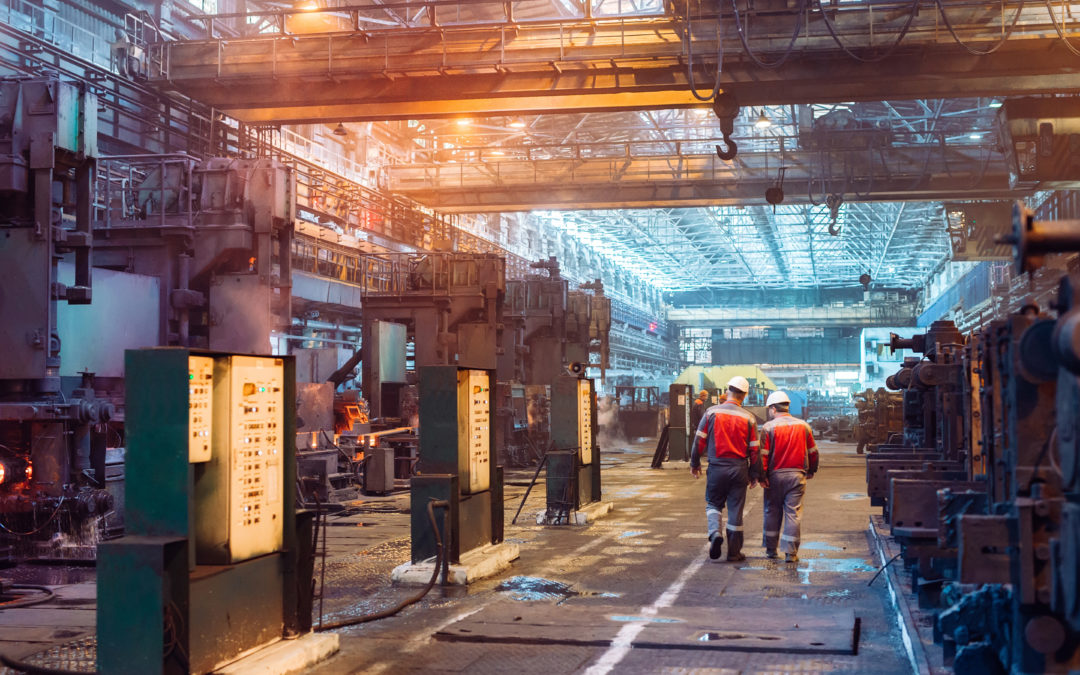 Workers walking through the interior of the steel mill. | A cover photo for a blog post about ICS/OT Incident Response from Dragos